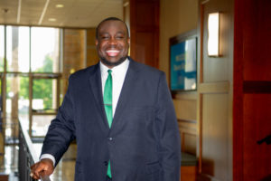man wearing a blue blazer and a green tie while smiling and standing indoors